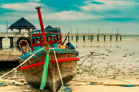 Fishing boat on sand beach near the bridge and sea. Relaxation on paradise tropical beach and resort concept. Garbage on the beach. Coastal environmental pollution. Marine environmental problems. Stock Photo