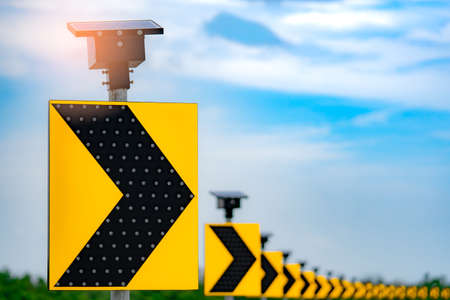 Traffic sign with solar cell panel power on blue sky and clouds background. Electric pole with solar energy. Green energy concept. Renewal energy. Alternative electricity source. Sustainable resources