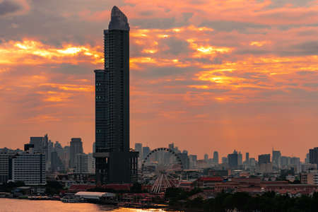 Cityscape of modern building near the river in the morning with orange sunrise sky and clouds at Bangkok in Thailand. Modern architecture office building city scape.