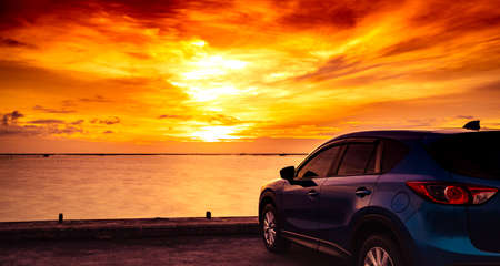 Blue compact SUV car with sport and modern design parked on concrete road by the sea at sunset. Hybrid auto and automotive concept. Road trip and car driving for travel. Car parked near the beach.