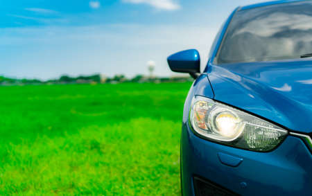 Front view of luxury blue compact SUV car with sport and modern design parked on green grass field with blue sky and white clouds. Hybrid auto and automotive. Road trip and car driving for travel. Imagens