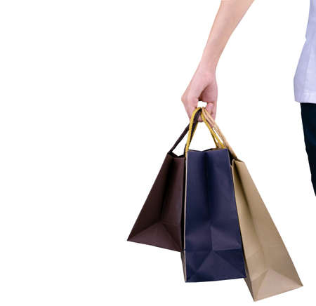 Woman carrying paper shopping bags isolated on white background. Adult woman hand hold three shopping bag with blue and brown color. Customer and shopping bag. Woman buy gift for friends or husband. Standard-Bild