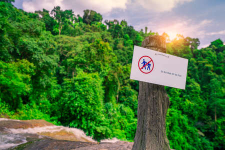 Do not walk of the trail. Warning sign in national park hang on concrete pole at waterfall in green tropical forest. Warning sign for traveler for prevent accident during trail. Sign for safety. 스톡 콘텐츠