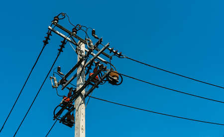 High voltage electric pole and transmission lines with clear blue sky. Electricity pylons. Power and energy engineering system. Danger high voltage tower. Cable wire on electric post. Power industry.