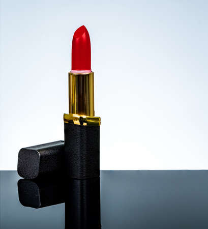 Red matte lipstick in gold and black tube package put on dark table isolated on white background in studio. Red lipstick with open cap. Makeup beauty cosmetic for confident fashion women. Archivio Fotografico