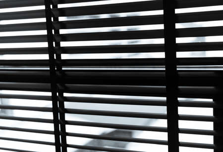Opened venetian plastic blinds in black and white. Plastic window with blinds. Interior design of living room with window horizontal blinds. Window slatted shades made of plastic. Hopeless and despair