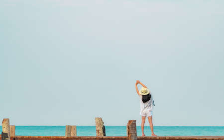 Back view of happy young Asian woman in casual style fashion and straw hat relax and enjoy holiday at tropical paradise beach. Girl standing at the wooden pier of resort in summer vacation fashion.