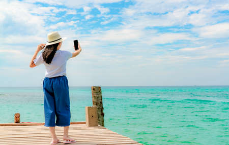 Young Asian woman wear straw hat in casual style use smartphone taking selfie at wooden pier. Summer vacation at tropical paradise beach. Happy girl travel on holiday. Woman enjoy and relax life. Imagens