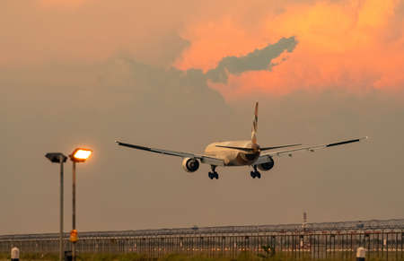 Commercial airline. Passenger plane landing at airport with beautiful sunset  sky and clouds. Arrival flight. Airplane flying over runway. Fence and taxiway lighting for safety flight in the evening.