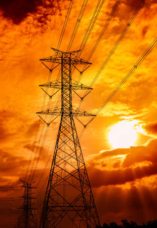 High voltage electric pole and transmission lines. Electricity pylons at sunset. Power and energy. Energy conservation. High voltage grid tower with wire cable at distribution station. Golden sky. Stock Photo