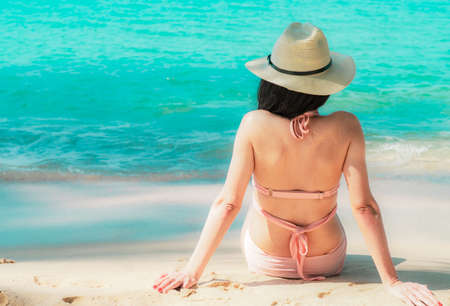 Back view of happy young Asian woman in pink swimsuit and straw hat relax and enjoy holiday at tropical paradise beach at sunset. Girl in summer vacation fashion. Beauty sexy model. Summer vibes.