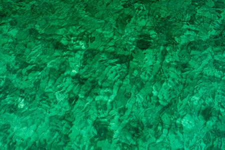 Green abstract texture background of emerald green sea water. Top view of green sea water with unique pattern. Green background. Sea water wave surface at coast. Turquoise water at shallow sea.