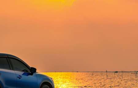 Blue compact SUV car with sport and modern design parked on concrete road by the sea at sunset. Environmentally friendly technology. Electric car technology and business. Hybrid auto and automotive. Stock fotó