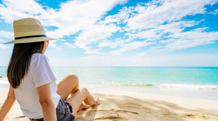 Happy young woman in white shirts and shorts sitting at sand beach. Relaxing and enjoying holiday at tropical paradise beach with blue sky and clouds. Girl in summer vacation. Summer vibes. Happy day. 版權商用圖片