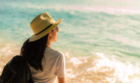 Back view of happy young Asian woman in casual style fashion with straw hat and backpack. Relax and enjoy holiday at tropical paradise beach. Summer vibes. Relaxing and enjoying at tropical beach. Stok Fotoğraf