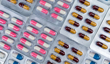 Top view of colorful antibiotic capsule pills in blister pack. Antibiotic drug resistance. Pharmaceutical industry. Pharmacy drug store background. Global health care concept. Antimicrobial capsule.