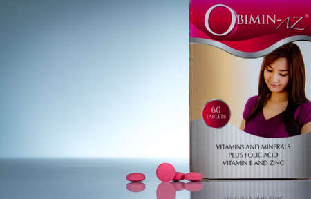 CHONBURI, THAILAND-OCTOBER 27, 2018 : Obimin-AZ. Vitamins and minerals plus folic acid vitamin E and zinc in drug bottle on gradient background. Pink tablets pills for during and after pregnancy woman 報道画像