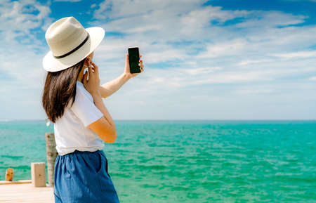 Young Asian woman wear hat in casual style use smartphone taking selfie at pier. Summer vacation at tropical paradise beach. Happy girl travel on holiday. Woman enjoy and relax life. Summer vibes.