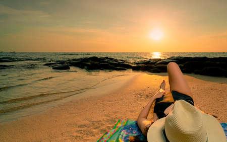 Frau, die sich bei Sonnenaufgang am Sandstrand hinlegt. Frau mit Strohhut, die am tropischen Paradiesstrand mit schönem Sonnenaufganghimmel ein Sonnenbad nimmt. Sommerurlaub. Mädchen tragen schwarzen Badeanzug schlafen am Sandstrand. Standard-Bild