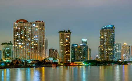 Stadtbild des modernen Gebäudes in der Nähe des Flusses in der Nacht. Bürogebäude der modernen Architektur. Wolkenkratzer mit Abendhimmel. Nachtfotografie des Gebäudes am Flussufer. Eigentumswohnung offenes Licht in der Nacht. Standard-Bild