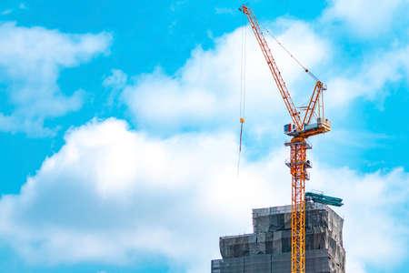 Plac budowy z dźwigiem i budynkiem. Przemysł nieruchomościowy. Dźwig używa sprzętu do podnoszenia szpuli na placu budowy. Budynek wykonany ze stali i betonu. Praca żurawia na tle błękitnego nieba i białej chmury Zdjęcie Seryjne