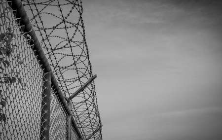Prison security fence. Barbed wire security fence. Razor wire jail fence. Barrier border. Boundary security wall.  Prison for arrest criminal or terrorist. Private area. Life without freedom concept.