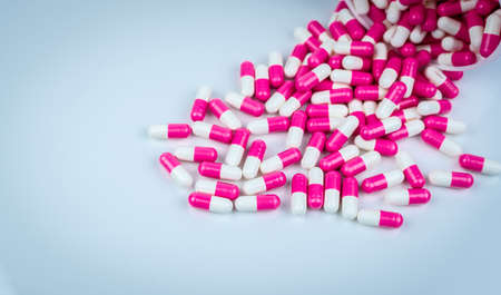 Pink and white capsules pill spilled out from white plastic bottle container. Global healthcare concept. Antibiotics drug resistance. Antimicrobial capsule pills. Pharmaceutical industry. Pharmacy.