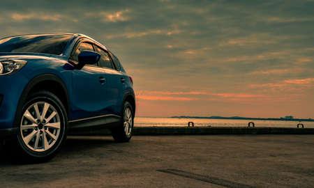 Voiture SUV compacte bleue avec sport et design moderne garée sur une route en béton au bord de la mer au coucher du soleil le soir. Concept de technologie de voiture hybride et électrique. Place de parking. Industrie automobile. Banque d'images