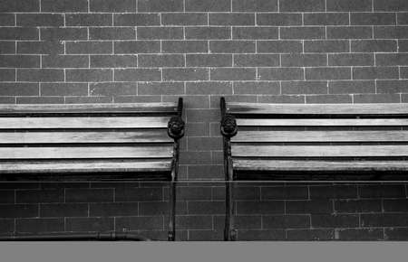 Empty couple wooden bench on grey brick wall background. Lonely and melancholy emotion concept. Background for sad, sorrow, tranquil and silence. Waiting for someone to full fill empty wooden chair. Stock Photo