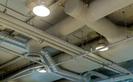 Kanał powietrzny, okablowanie i hydraulika w centrum handlowym. Rura klimatyzatora, rura okablowania i system rur wodociągowych. Koncepcja wnętrza budynku. Lampa sufitowa z otwartym światłem. Koncepcja architektury wnętrz. Zdjęcie Seryjne