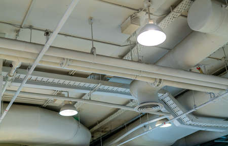 Air duct, wiring and plumbing in the mall. Air conditioner pipe, wiring pipe, and plumbing pipe system. Building interior concept. Ceiling lamp light with opened light. Interior architecture concept. 版權商用圖片