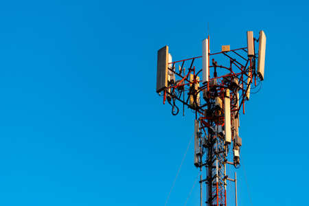 Telecommunication tower with clear blue sky background. Antenna on blue sky background. Radio and satellite pole. Communication technology. Imagens