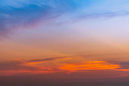 Dramatic blue and orange sky and clouds abstract background. Red-orange clouds on sunset sky. Warm weather background. Art picture of sky at dusk. Sunset abstract background. Dusk and dawn concept