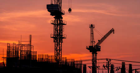 Construction site with crane and sunset sky. Real estate industry. Crane use reel lift up equipment in construction site. Building made of steel and concrete. Crane work against orange sunset sky.