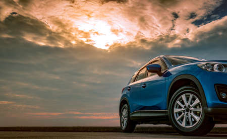 Blue compact SUV car with sport and modern design parked on concrete road by the sea at sunset in the evening. Hybrid and electric car technology concept. Car parking space. Automotive industry. Reklamní fotografie