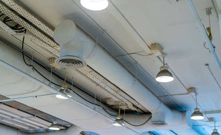 Air duct, wiring and plumbing in the mall. Air conditioner pipe, wiring pipe, and plumbing pipe system. Building interior concept. Ceiling lamp light with opened light. Interior architecture concept. Фото со стока