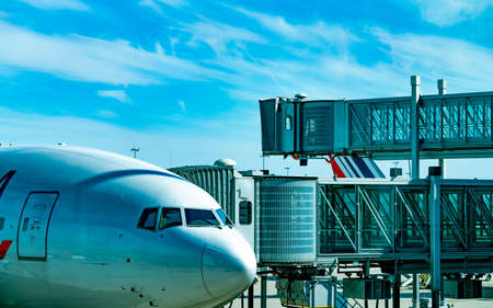 Commercial airline parked at jet bridge for passenger take off at the airport. Aircraft passenger boarding bridge docked with blue sky and white clouds. Departure flight of international airline.