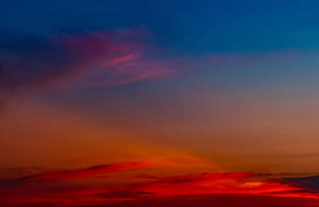 Dramatic red and blue sky and clouds abstract background. Red-blue clouds on sunset sky. Warm weather background. Art picture of sky at dusk. Sunset abstract background. Sad dramatic sunset sky.