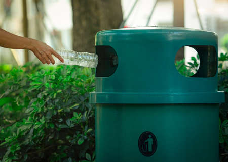 People hand throwing empty water bottle in recycle bin at park. Green plastic recycle bin. Man discard bottle in trash bin. Waste management. Plastic bottle garbage. Reduce and reuse plastic concept.