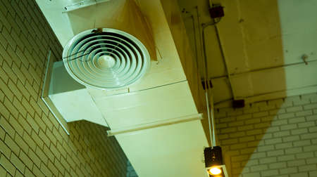 Air duct on ceiling. Air conditioner pipe system. Air ventilation system. Air heading unit on wall. Cool system in building. Building interior architecture concept. Ceiling lamp with opened light. Фото со стока