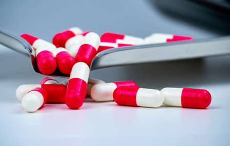 Red-white antibiotic capsule pills on stainless steel drug tray. Antimicrobial capsule pills. Pharmacy drugstore background. Pharmaceutics concept. Pharmaceutical industry. Pharmaceutical products.