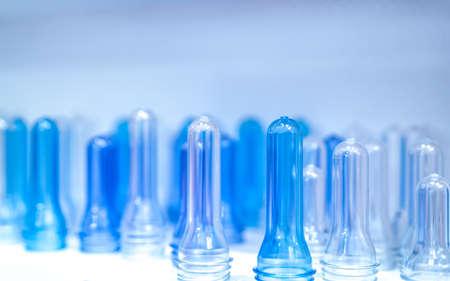 Preformas de botellas de PET antes del proceso de moldeo por soplado, llenado y etiquetado. Preformas de botellas de PET azul para la industria de bebidas. Materia prima para botella PET con empaque de rosca. Reciclar el concepto de plástico.