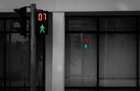 Pedestrian signals on traffic light pole. Pedestrian crossing sign for safe to walk in the city. Crosswalk signal. Green traffic light signal and 7 seconds left to walk across the road. 免版税图像