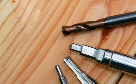 Special tools isolated on wooden table. Made to order special tools. Coated step drill and reamer detail. HSS cemented carbide. Carbide cutting tool for industrial applications. Engineering tools.