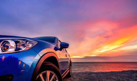 Blue compact SUV car with sport and modern design parked by beach at sunset. Hybrid and electric car technology. Car parking space. Automotive industry. Car care business background. Beautiful sky. Reklamní fotografie