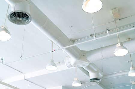 Luchtkanaal, airconditioningpijp, bedradingspijp en sprinklersysteem. Luchtstroom en ventilatiesysteem. Gebouw interieur. Plafondlamp licht met geopend licht. Interieur architectuurconcept.