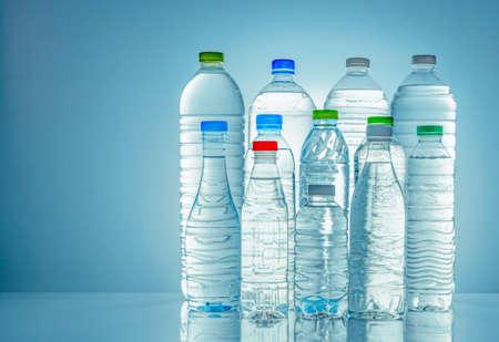 Conjunto de botella de agua de plástico transparente con etiqueta en blanco. Botella de agua clara y minerales naturales con tapón blanco, verde, rojo y azul. Bebida saludable. Colección de botella de plástico con líquido completo.