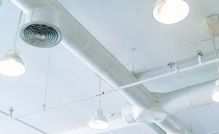 Air duct, air conditioner pipe and fire sprinkler system on white ceiling wall. Air flow and ventilation system. Building interior. Ceiling lamp light with opened light. Interior architecture concept.