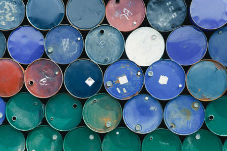 Old chemical barrels. Blue, green, and red oil drum. Steel oil tank. Toxic waste warehouse. Hazard chemical barrel with warning label. Industrial waste in metal drum. Hazard waste storage in factory.