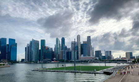 SINGAPORE-MAY 19, 2019 : Cityscape Singapore modern and financial city in Asia. Marina bay landmark of Singapore. Landscape of business building. People walking travel near floating football pitch.